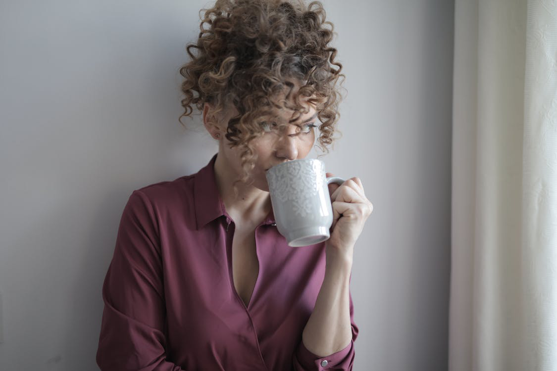 a young woman drinking coffee and introspecting in a casual home setting